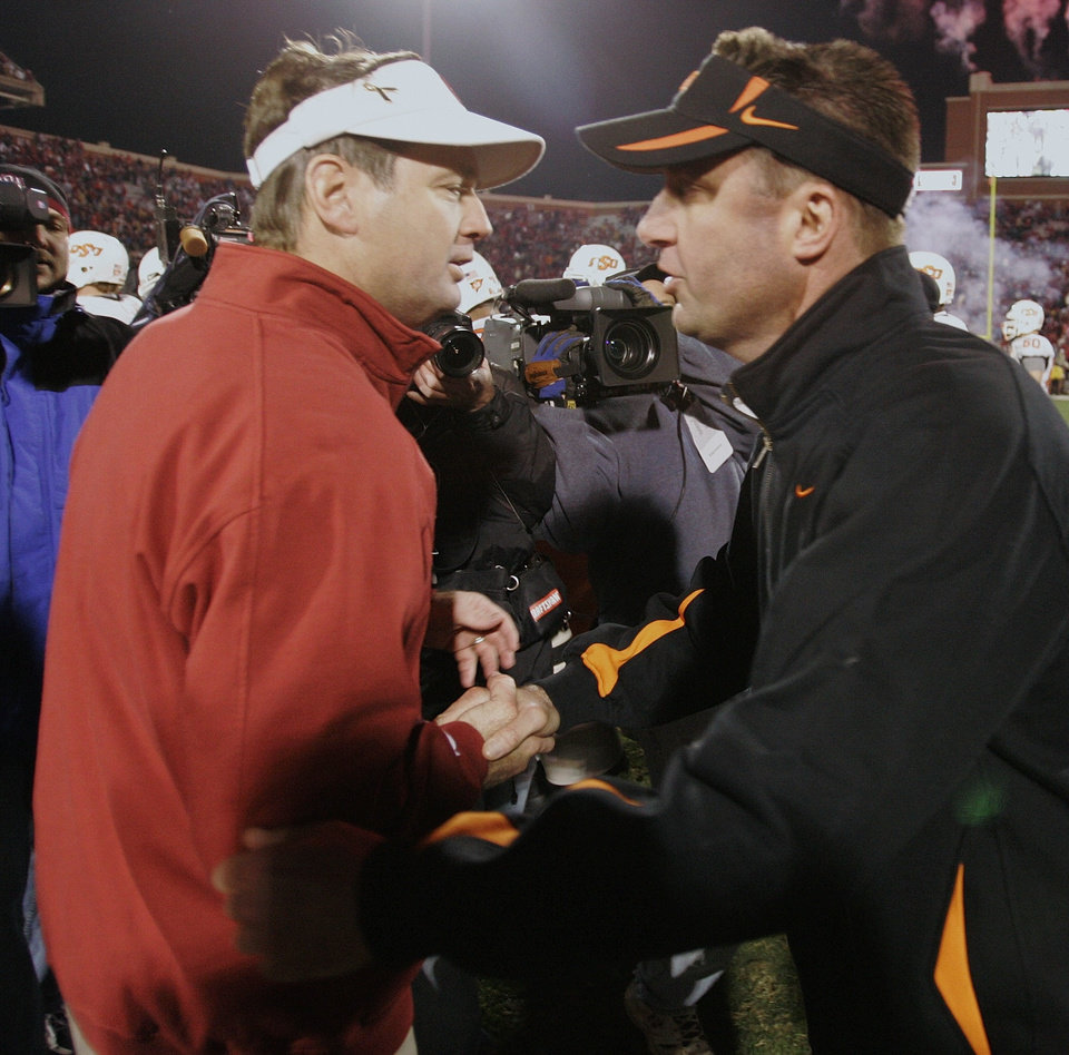 Photo - BEDLAM, OU, OSU: University of Oklahoma head coach Bob Stoops, left, and Oklahoma State University head coach Mike Gundy, right, shake hands at midfield following their college football game in Norman, Okla., Saturday, Nov. 24, 2007. Oklahoma won the game 49-17. (AP Photo/Sue Ogrocki)  ORG XMIT: OKSO108