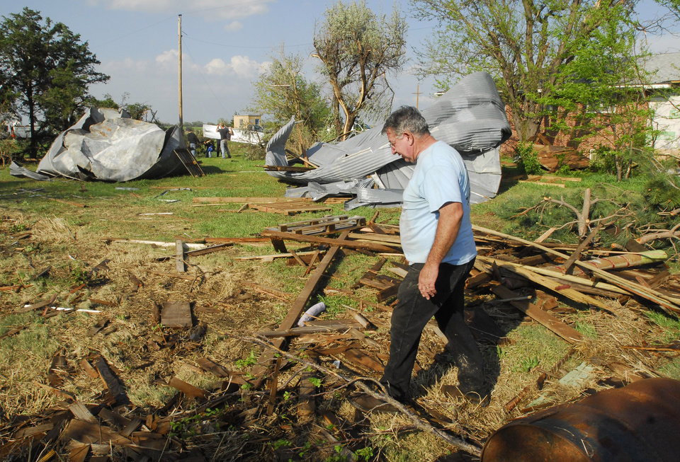 Photo -   Blaine Hyatt, Rush Center, walks around his yard on Saturday, April 14, 2012, about a mile east of Rush Center, Kan., after a tornado damaged his home, destroyed several outbuildings and two grain bins. (AP Photo/The Hays Daily News, Steven Hausler)