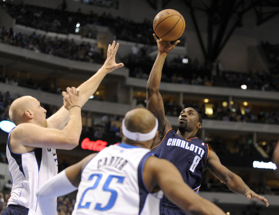 Charlotte Bobcats guard Ben Gordon (8) puts up a shot over Dallas Mavericks center Chris Kaman and guard Vince Carter (25) in the first half during an NBA basketball game on Saturday, Nov. 3, 2012, in Dallas. (AP Photo/Matt Strasen)