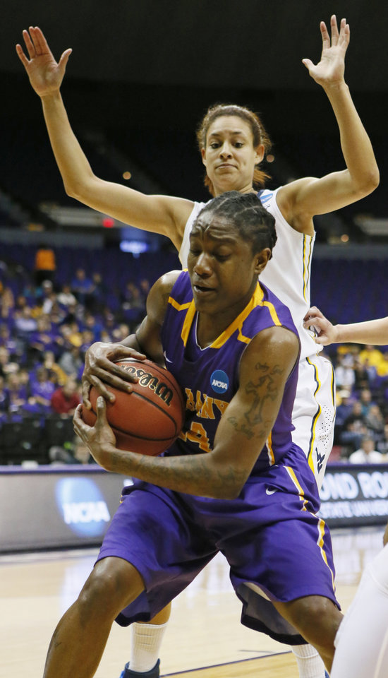 Photo - Albany guard Tammy Phillip (14) hauls down a rebound in front of West Virginia forward Jess Harlee in the first half of an NCAA college basketball first-round tournament game on Sunday, March 23, 2014, in Baton Rouge, La. (AP Photo/Rogelio V. Solis)
