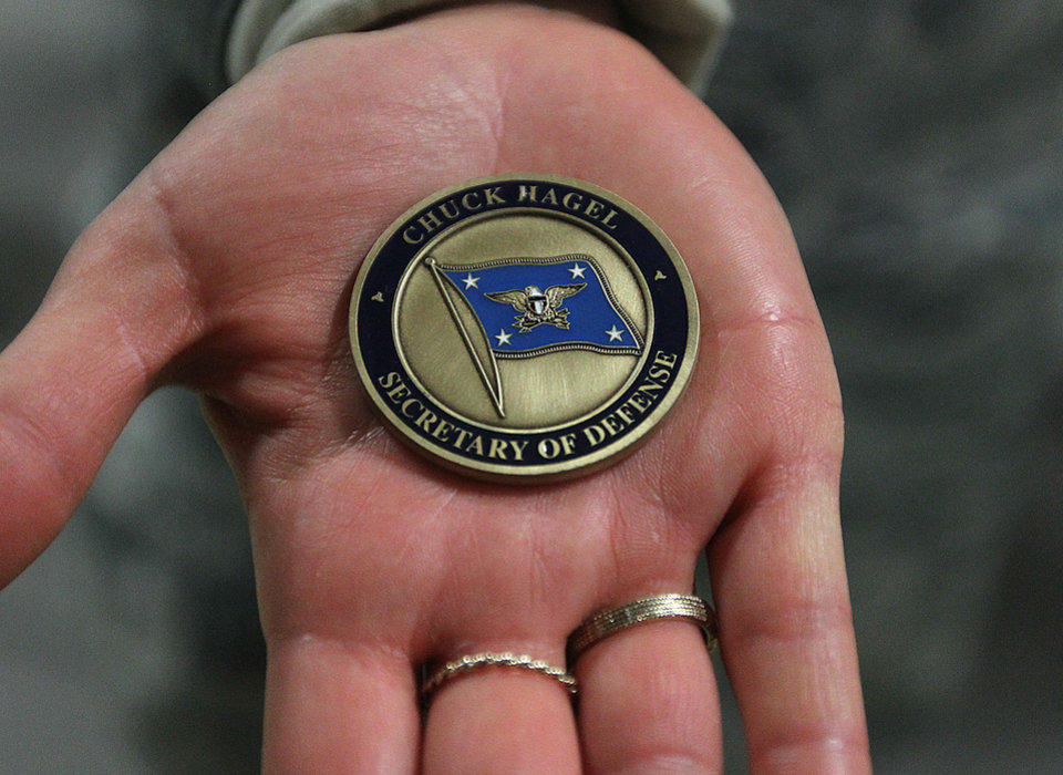 Photo - Lt. Christen Ornella holds out a military coin that were handed out to airmen attending the visit of Defense Secretary Chuck Hagel on Thursday, Jan. 9, 2014 at F.E. Warren Air Force Base in Cheyenne, Wyo. It was the first time since 1982 that a defense secretary has visited the nuclear missile base. (AP Photo/Wyoming Tribune Eagle, Blaine McCartney)