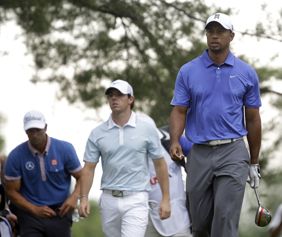 Photo - Tiger Woods, from right, Rory McIlroy, of Northern Ireland, and Adam Scott, of Australia, walk down from the fifth tee box during the first round of the U.S. Open golf tournament at Merion Golf Club, Thursday, June 13, 2013, in Ardmore, Pa. (AP Photo/Gene J. Puskar)