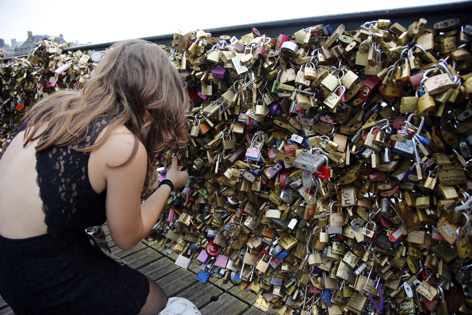 Photo - A tourist continues to fix a love padlock on the Pont des Arts bridge after a chunk of fencing with thousands of locks fell off under their weight in Paris, Monday, June 9, 2014. The thousands of locks that cling like barnacles to the Pont des Arts in Paris have become a symbol of danger, rather than love, after a chunk of fencing fell off under their weight. The fencing tumbled late Sunday on the pedestrian bridge, which crosses the Seine. (AP Photo/Francois Mori)