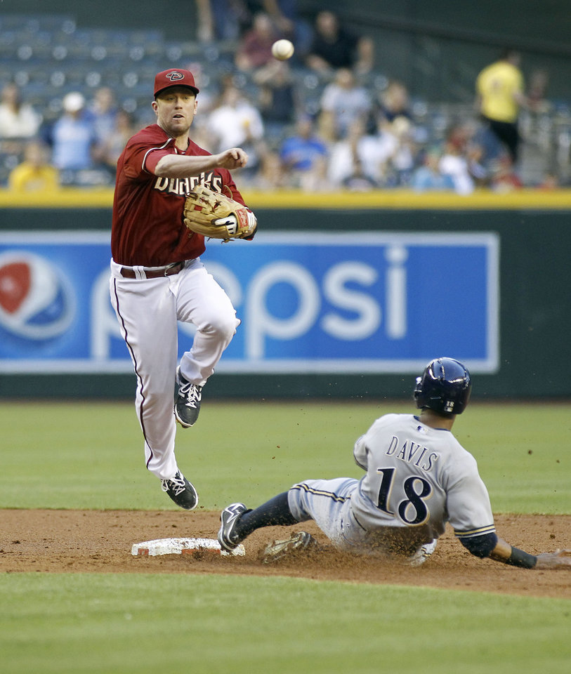 Photo - Arizona Diamondbacks second baseman Aaron Hill, left, throws to first to complete a double play after forcing out Milwaukee Brewers' Kris Davis, right, on a ground ball by Brewers' Mark Reynolds during the second inning of a baseball game on Wednesday, June 18, 2014, in Phoenix. (AP Photo/Ralph Freso)