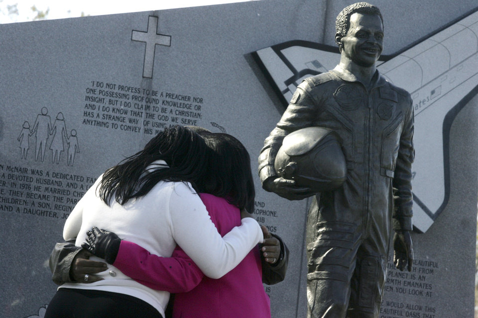 Photo - Joy McNair, left, daughter, Reginald McNair, son, and Cheryl McNair, wife, embrace under a statue of  Lake City, S.C., astronaut Ron McNair at Ron McNair Memorial Park in Lake City, in 2006. McNair died Jan. 28, 1986, along with six other astronauts when the space shuttle Challenger exploded. (AP Photo/Morning News, Heidi Heilbrunn)