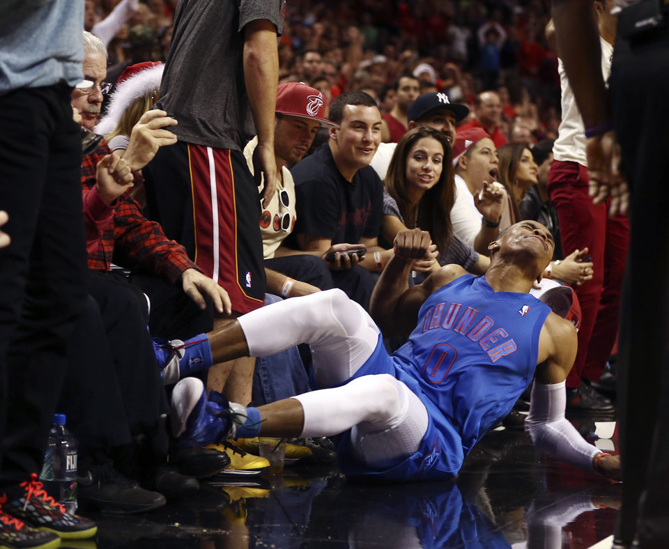 Photo - Fans watch as Oklahoma City Thunder's Russell Westbrook is charged with a foul against the Miami Heat during the second half of an NBA basketball game in Miami, Tuesday, Dec. 25, 2012. The Heat won 103-97. (AP Photo/J Pat Carter) ORG XMIT: FLJC118