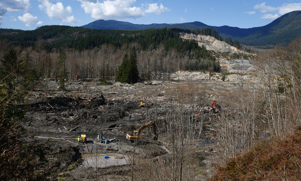 Photo - The scale of the mudslide's reach can be seen from an emergency and work access road, connecting Arlington to Darrington, as crews work to clear mud and debris at the west site of the mudslide on Highway 530, near Oso, Wash., on Tuesday, April 1, 2014. The death toll from the March 22 mudslide has increased to 28. (AP Photo/The Seattle Times, Lindsey Wasson)  SEATTLE OUT; USA TODAY OUT; MAGS OUT; TELEVISION OUT; NO SALES; MANDATORY CREDIT TO BOTH THE SEATTLE TIMES AND THE PHOTOGRAPHER