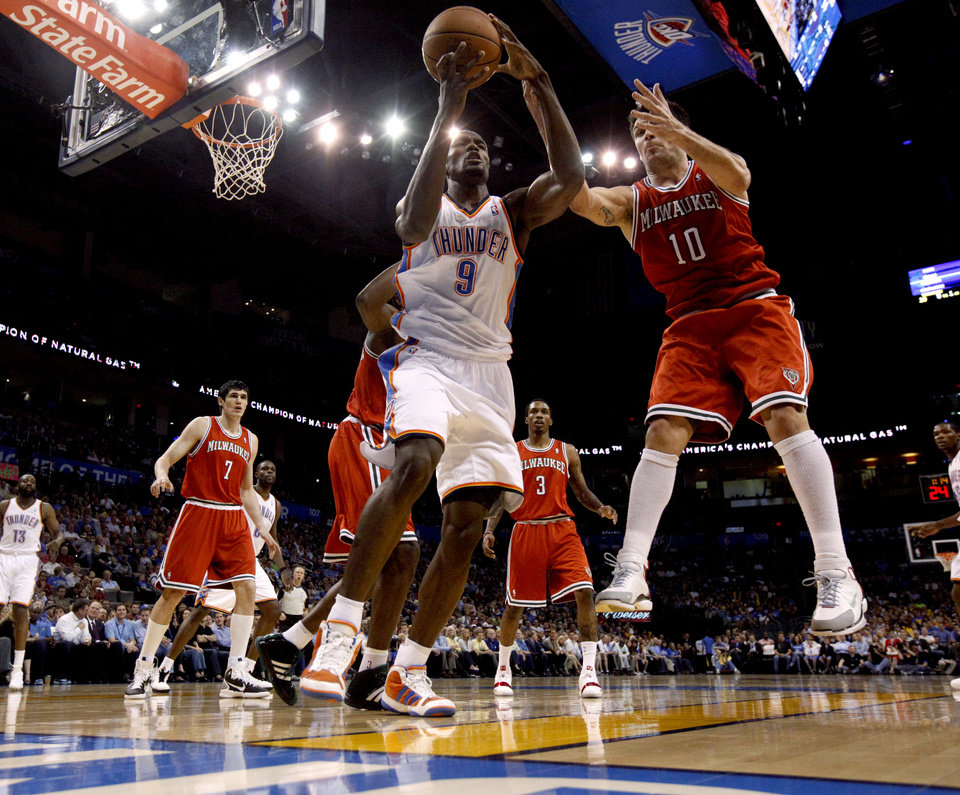 Photo - Oklahoma City's Serge Ibaka (9) goes for the ball beside Milwaukee's Carlos Delfino (10) during the NBA basketball game between the Oklahoma City Thunder and the Milwaukee Bucks at the Oklahoma City Arena, Wednesday, April 13, 2011. Photo by Bryan Terry, The Oklahoman