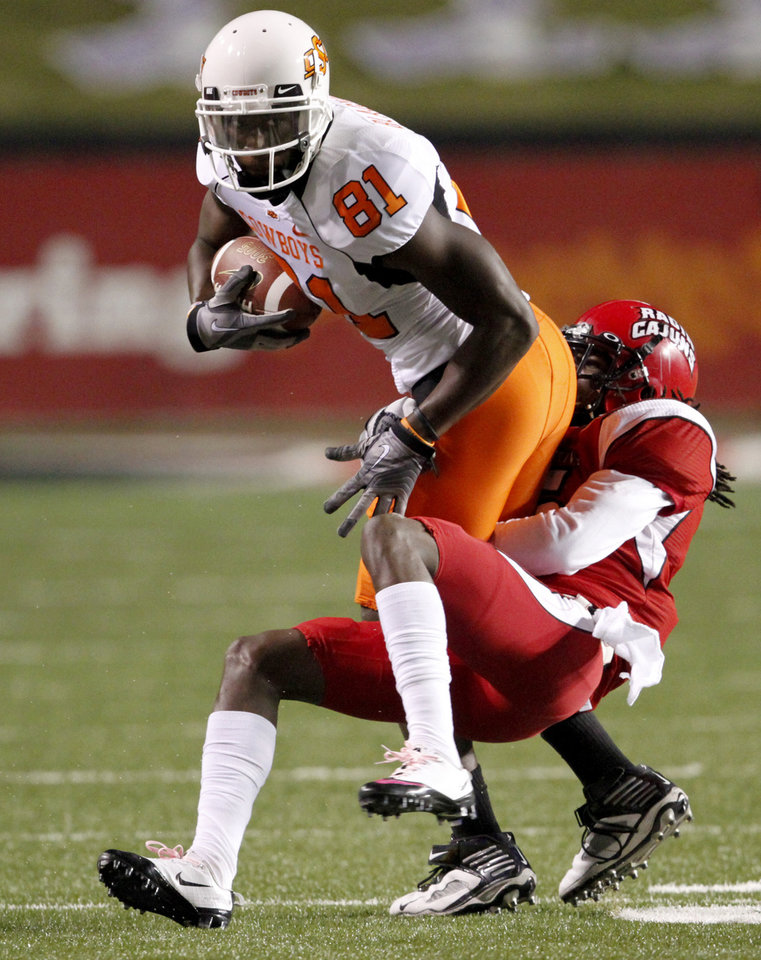 COLLEGE FOOTBALL: OSU's Justin Blackmon fights off Louisiana-Lafayette's Dwight Bentley on a return during the football game between the University of Louisiana-Lafayette and Oklahoma State University at Cajun Field in Lafayette, La., Friday, October 8, 2010. Photo by Bryan Terry, The Oklahoman ORG XMIT: KOD