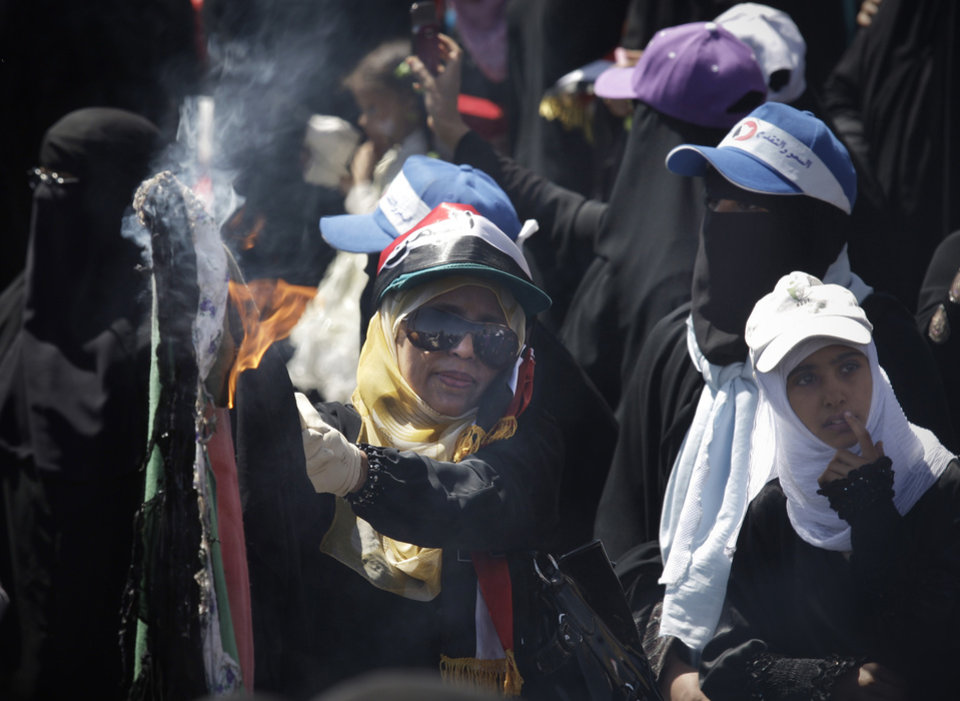 A female Yemeni protestor burns veils during a demonstration demanding the resignation of Yemeni President Ali Abdullah Saleh in Sanaa, Yemen, Wednesday, Oct. 26, 2011. The burning of the veil was not related to women\'s rights or issues surrounding the Islamic veils - rather, the act of women burning their clothing is a symbolic Bedouin tribal gesture signifying an appeal for help to tribesmen, in this case to stop the attacks on women protesters. (AP Photo/Hani Mohammed) ORG XMIT: CAI111