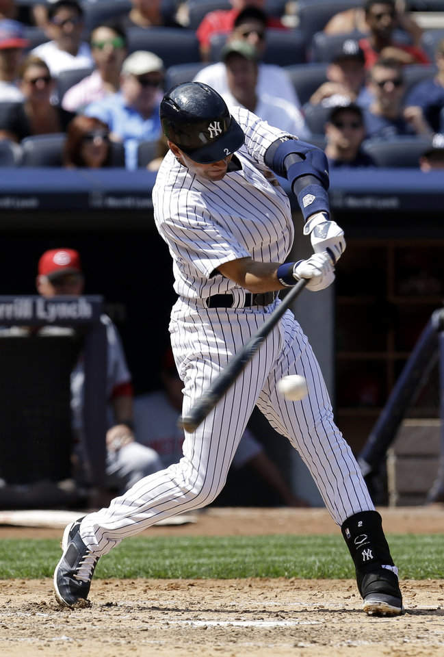 Photo - New York Yankees' Derek Jeter hits an RBI single during the fifth inning of a baseball game against the Cincinnati Reds at Yankee Stadium on Sunday, July 20, 2014, in New York. (AP Photo/Seth Wenig)