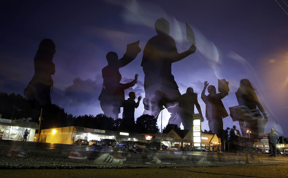 Photo - Protesters march in the street as lightning flashes in the distance in Ferguson, Mo. on Wednesday, Aug. 20, 2014. On Aug. 9, 2014, a white police officer fatally shot Michael Brown, an unarmed black 18-year old, in the St. Louis suburb. (AP Photo/Jeff Roberson)