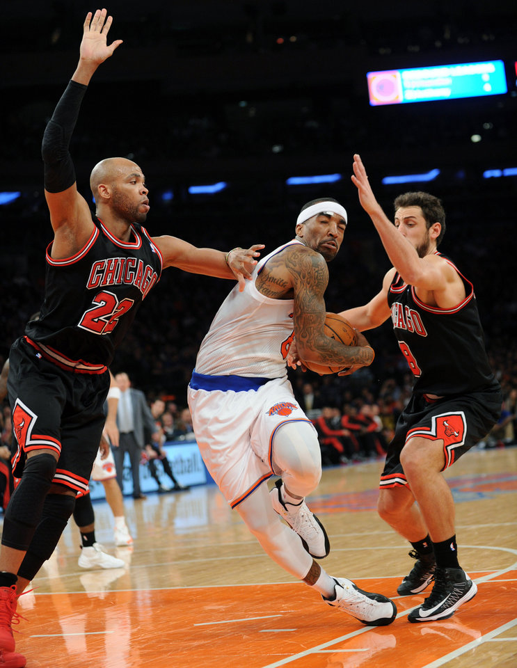 New York Knicks\' J.R. Smith attempts to drive to the basket between Chicago Bulls\' Taj Gibson, left, and Marco Belinelli, right, of Italy, during the first half of an NBA basketball game Friday, Jan. 11, 2013, at Madison Square Garden in New York. (AP Photo/Bill Kostroun)