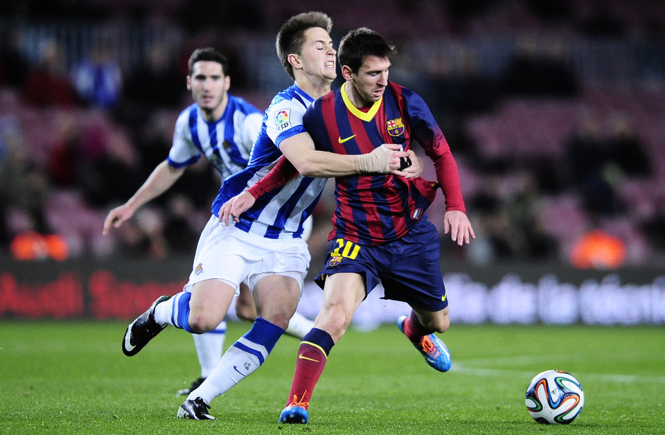 Photo - FC Barcelona's Lionel Messi, from Argentina, right, duels for the ball against Real Sociedad's Carlos Martinez during a Copa del Rey soccer match at the Camp Nou stadium in Barcelona, Spain, Wednesday, Feb. 5, 2014. (AP Photo/Manu Fernandez)