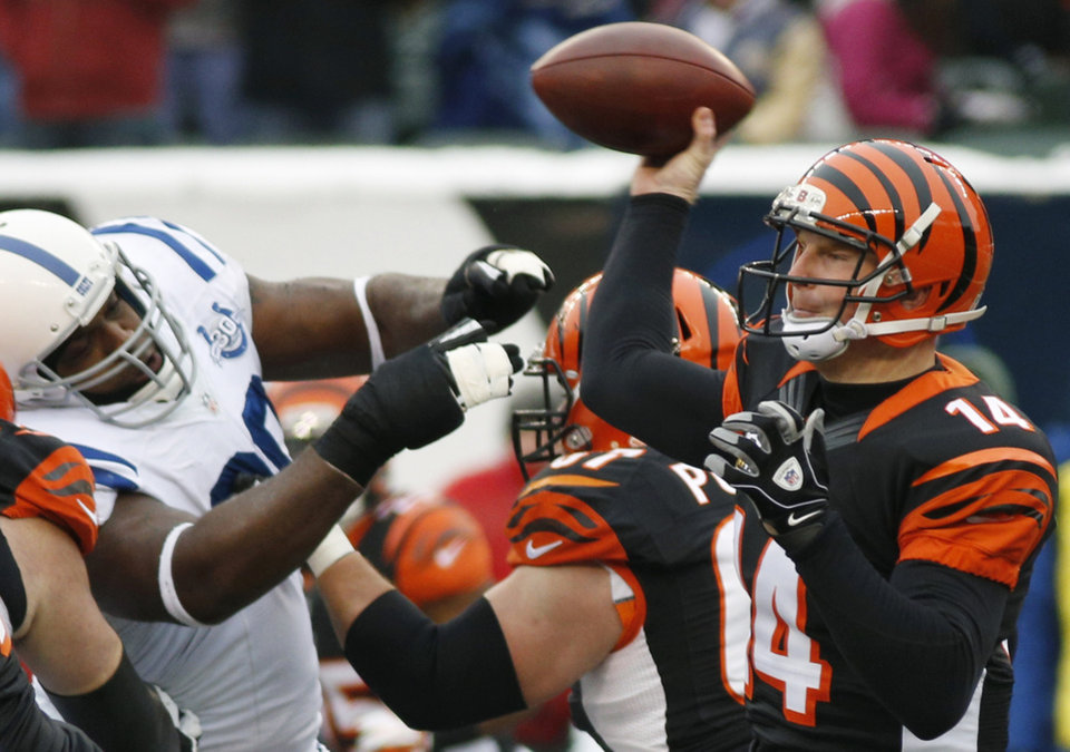 Photo - Cincinnati Bengals quarterback Andy Dalton (14) passes against the Indianapolis Colts in the first half of an NFL football game, Sunday, Dec. 8, 2013, in Cincinnati. (AP Photo/David Kohl)