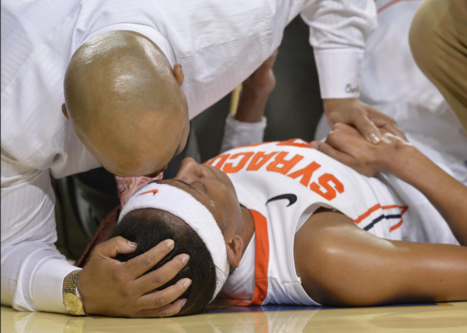 Photo - Syracuse head coach Quentin Hillsman, top, comforts Brittney Sykes following her knee injury during the second half of a first-round game in the NCAA college basketball tournament in Lexington, Ky., Saturday, March 22, 2014. Syracuse defeated Chattanooga 59-53. (AP Photo/Timothy D. Easley)