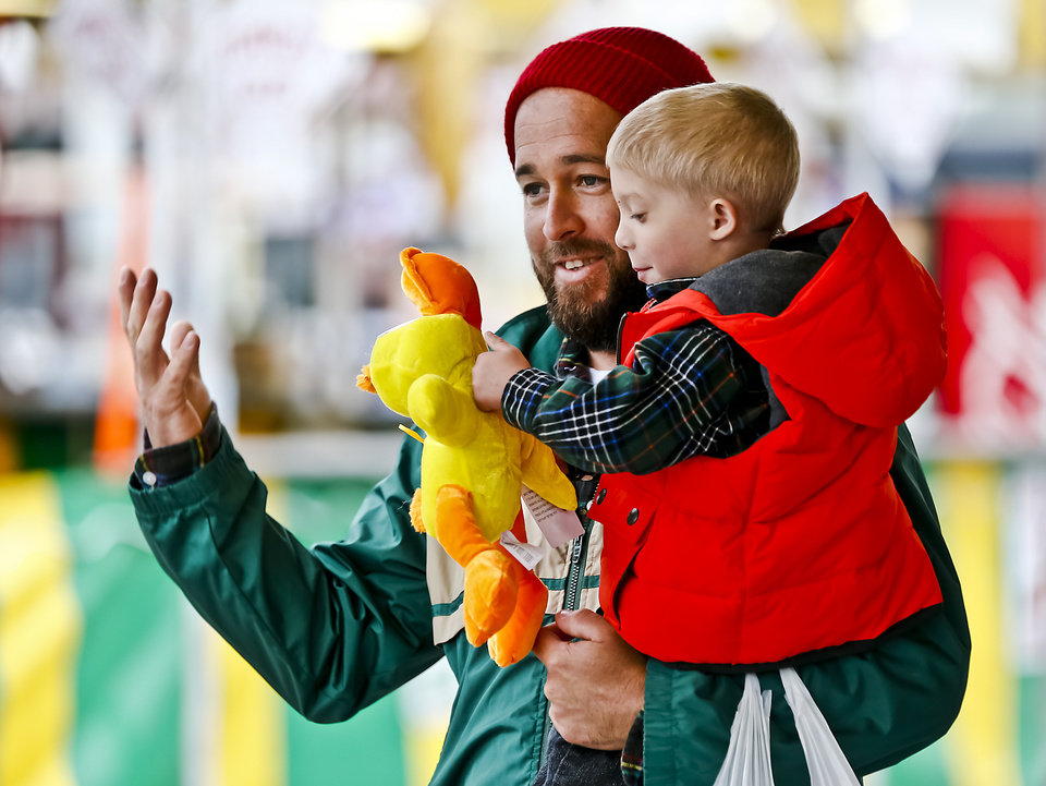 Photo - Chris Whitworth and his son Cooper celebrate their stuffed animal winnings after playing a game on the midway at the Oklahoma State Fair at State Fair Park on Friday, Sept. 14, 2012, in Oklahoma City, Oklahoma.  Photo by Chris Landsberger, The Oklahoman