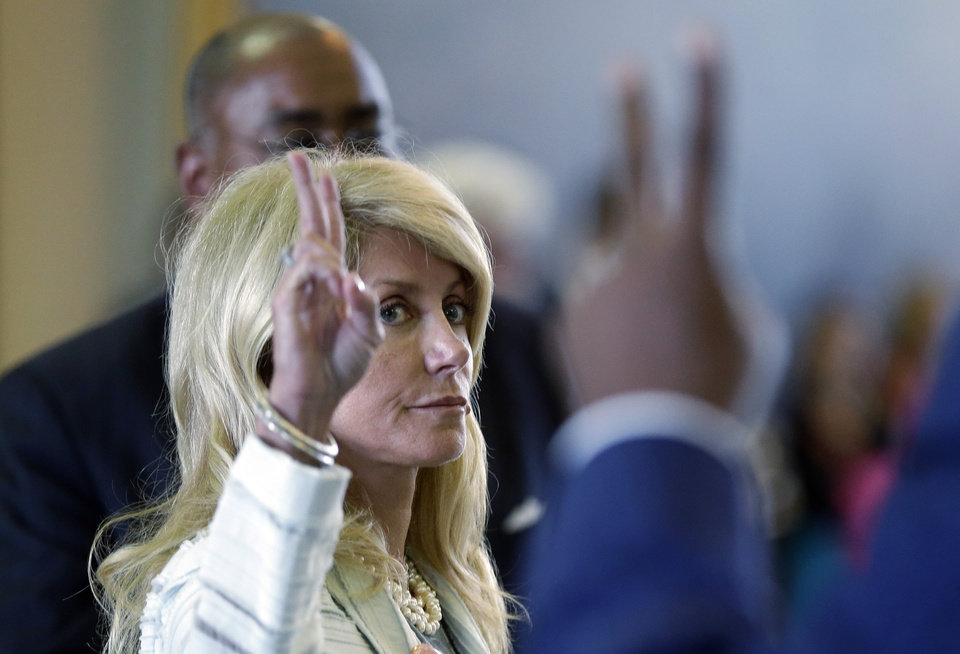 Photo - Sen. Wendy Davis, D-Fort Worth, left, votes against a motion to call for a rules violation during her filibusters of an abortion bill, Tuesday, June 25, 2013, in Austin, Texas. Davis was given a second warning for breaking filibuster rules by receiving help from Sen. Rodney Ellis, D-Houston, with a back brace. (AP Photo/Eric Gay)