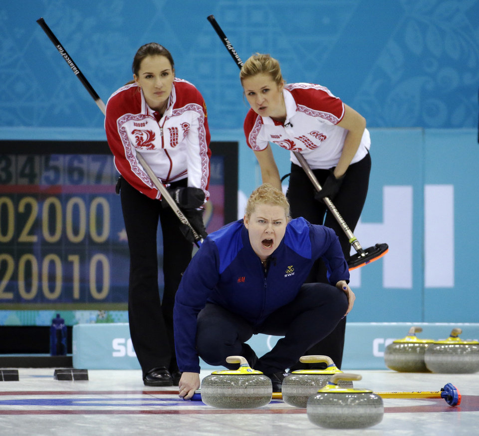 Photo - Sweden's Margaretha Sigfridsson yells to sweepers as Russia's Anna Sidorova, left, and Margarita Fomina watch during a round robin session against the United States at the 2014 Winter Olympics, Sunday, Feb. 16, 2014, in Sochi, Russia. (AP Photo/Morry Gash)