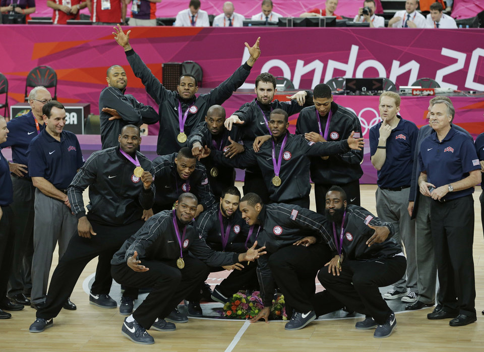 Members of the United States men's basketball team display the gold medal during a ceremony at the 2012 Summer Olympics, Sunday, Aug. 12, 2012, in London. (AP Photo/Matt Slocum)