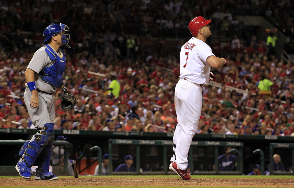 Photo - St. Louis Cardinals' Matt Holliday, right, and Los Angeles Dodgers catcher A.J. Ellis watch Holliday's two-run home run during the fifth inning of a baseball game Friday, July 18, 2014, in St. Louis. (AP Photo/Jeff Roberson)