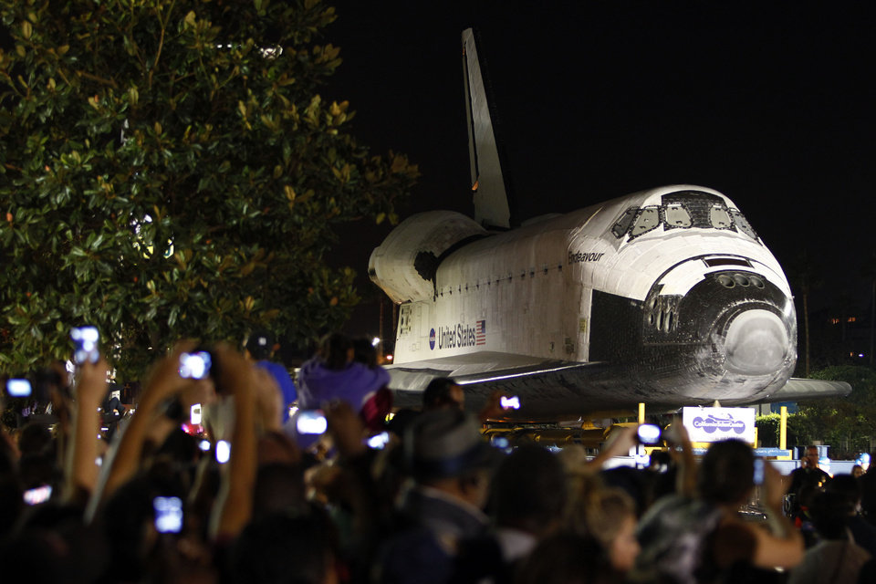 Photo -   Spectators take pictures as the space shuttle Endeavour makes its way through city streets in Los Angeles, Calif., Saturday, Oct. 13, 2012. Endeavour's 12-mile road trip kicked off shortly before midnight Thursday as it moved from its Los Angeles International Airport hangar en route to the California Science Center. (AP Photo/Patrick T. Fallon)