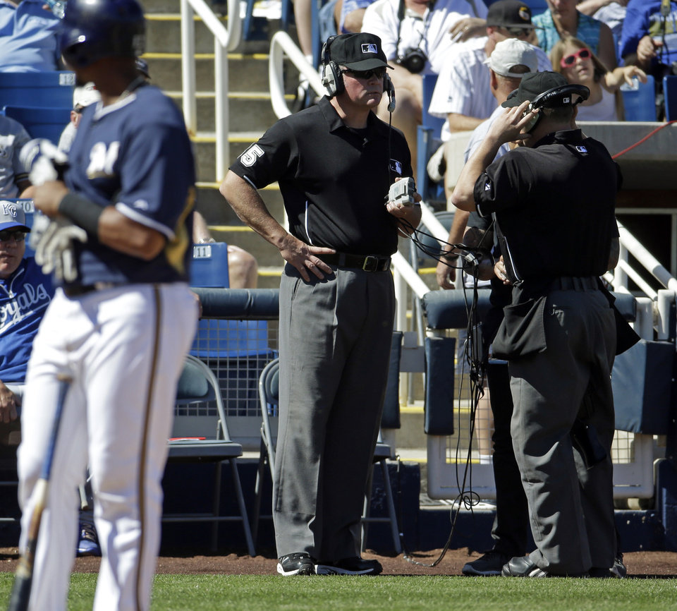 Photo - Umpires Ted Barrett, left, and Alan Bailey review a call during an exhibition spring training baseball game between the Milwaukee Brewers and the Kansas City Royals Saturday, March 8, 2014, in Phoenix. (AP Photo/Morry Gash)