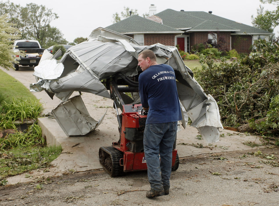 Photo - Homeowner Mike Paschal transports part of what's left of his metal building to the street in the Dripping Springs Estates Saturday, May 15, 2010. Saturday hundreds of volunteers went into areas that had been affected by last week's tornadoes to help clear debris. Photo by Doug Hoke, The Oklahoman.