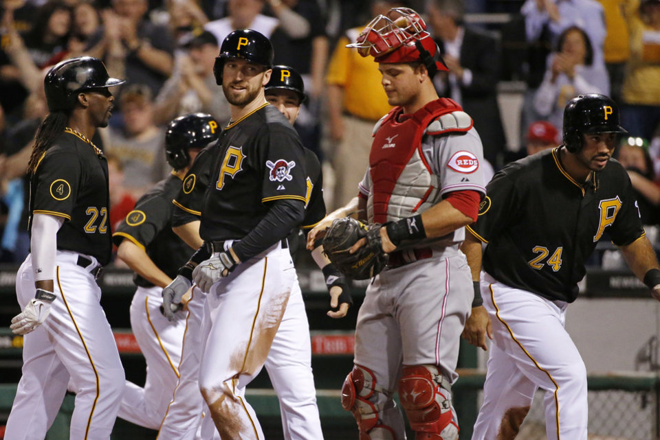 Photo - Pittsburgh Pirates' Ike Davis, second from left, celebrates with teammates from left, Andrew McCutchen, Neil Walker, rear,  and Pedro Alvarez (24), who were on base for his first home run with the Pirates, a grand slam off Cincinnati Reds starting pitcher Mike Leake as Cincinnati Reds catcher Devin Mesoraco watches the scoreboard replay, during the fourth inning of a baseball game in Pittsburgh Monday, April 21, 2014. (AP Photo/Gene J. Puskar)