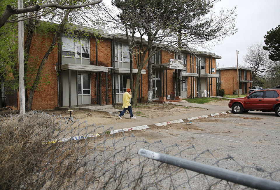 A man walks in front of the dilapidated Courtyard Apartments at 3732 in northwest Oklahoma City. Photo by Jim Beckel, The Oklahoman <strong>Jim Beckel</strong>