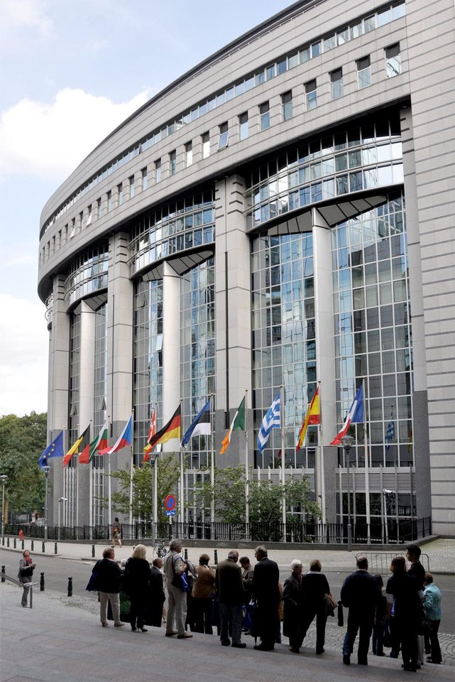 Tourists view the glassy facade of the Paul-Henri Spaak Building, home of the European Parliament in Brussels.    Photo by Rick Steves  <strong>Photo by Rick Steves</strong>