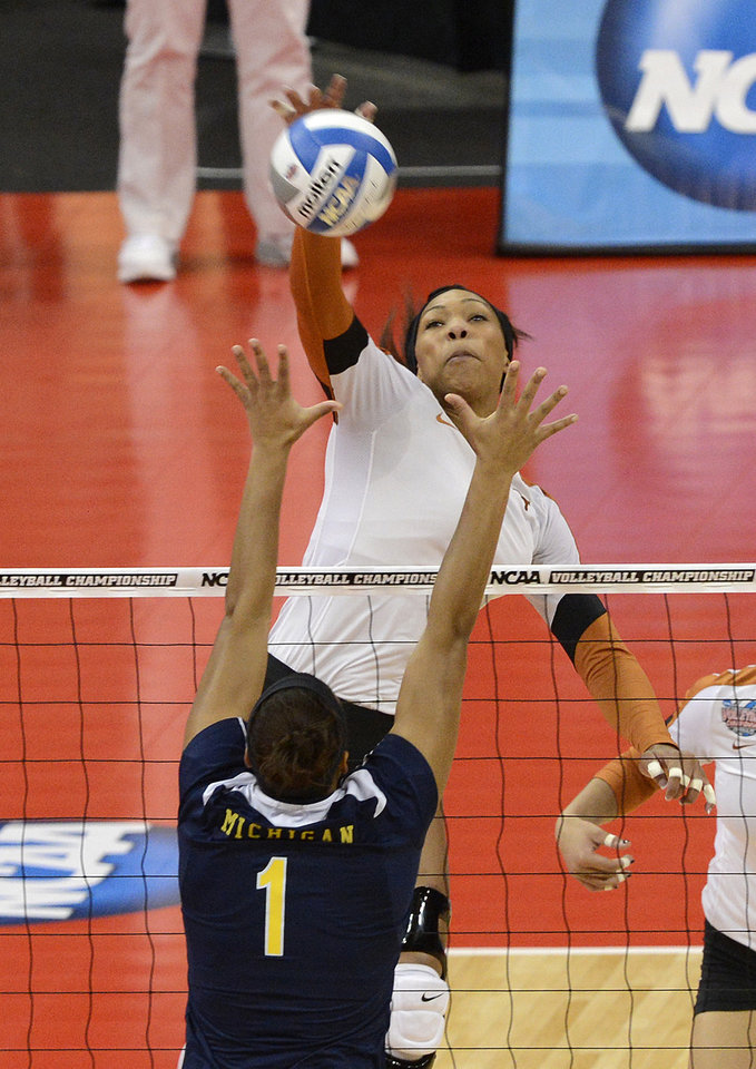 Texas' Khat Bell, rear, spikes the ball through the defense of Michigan's Molly Toon during the national semifinals of the NCAA college women's volleyball tournament Thursday, Dec. 13, 2012 in Louisville, Ky. (AP Photo/Timothy D. Easley)