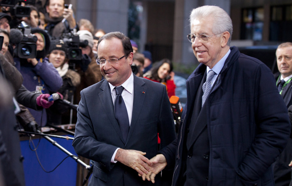 Photo - French President Francois Hollande, center left, shakes hands with Italian Prime Minister Mario Monti as they arrive for an EU summit in Brussels on Thursday, Dec. 13, 2012. In one whirlwind morning, the European Union nations agreed on the foundation of a fully-fledged banking union and Greece's euro partners approved billions of euros in bailout loans that will prevent the nation from going bankrupt. (AP Photo/Virginia Mayo)