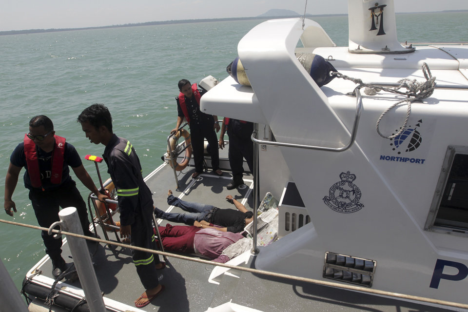 Photo - EDS NOTE: GRAPHIC CONTENT - In this photo released by Malaysian Maritime Enforcement Agency, Malaysian marine police officers stand on the deck of a boat after they retrieved bodies of a capsized boat off Sungai Air Hitam in Banting, outside Kuala Lumpur, Malaysia, Wednesday, June 18, 2014. At least 60 people survived when a wooden boat carrying 97 Indonesians capsized and sank early Wednesday after leaving Malaysia's west coast, but 32 others are still missing and five bodies have been recovered, Malaysia's maritime agency said. (AP Photo/Malaysian Maritime Enforcement Agency) EDITORIAL USE ONLY