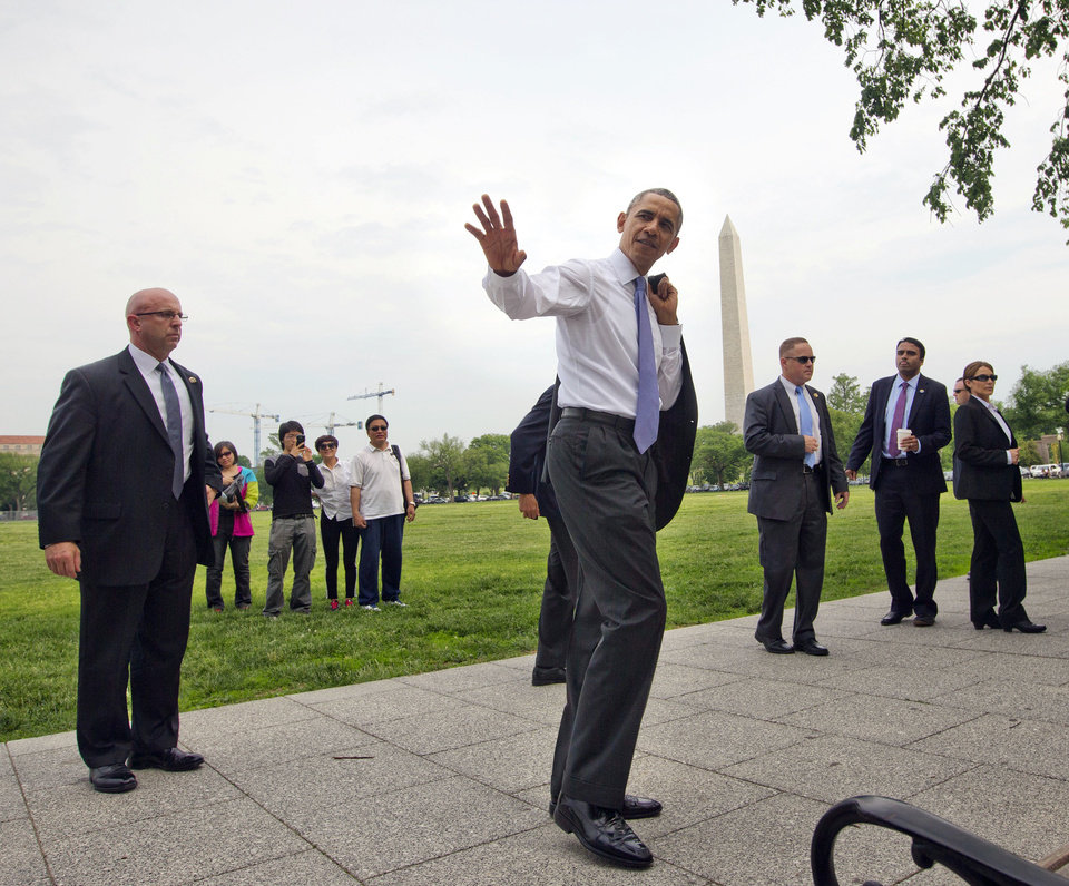 President Barack Obama waves to tourists during his surprise walk along the Ellipse in Washington, Wednesday, May 21, 2014. Obama walked to the Department of the Interior to sign a proclamation regarding the Organ Mountains-Desert Peaks National Monument. (AP Photo/Pablo Martinez Monsivais)