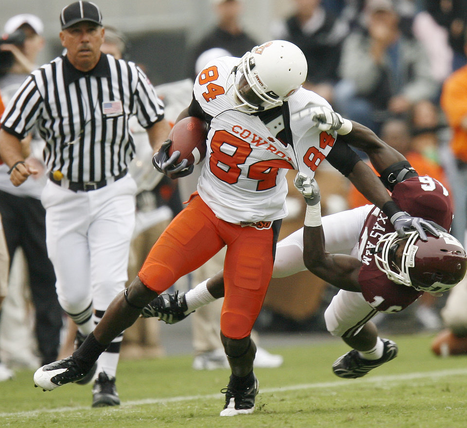 Photo - OSU's Hubert Anyiam fights off Steven Campbell of Texas A&M during the college football game between Oklahoma State University (OSU) and Texas A&M University at Kyle Field in College Station, Texas, Saturday, October 10, 2009. Photo by Bryan Terry, The Oklahoman ORG XMIT: KOD