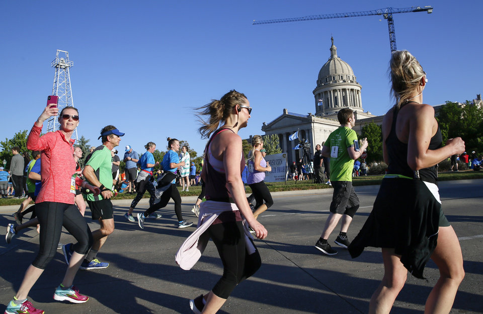 Photo - Runners pass the state Capitol on Lincoln Blvd. during the Oklahoma City Memorial Marathon in Oklahoma City, Sunday, April 28, 2019. [Nate Billings/The Oklahoman]