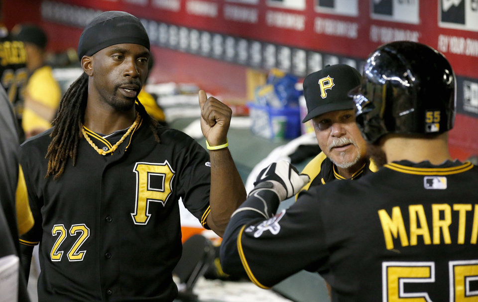 Photo - Pittsburgh Pirates' Andrew McCutchen (22) congratulates teammate Russell Martin, right, after Martin scored a run against the Arizona Diamondbacks during the second inning of a baseball game on Sunday, Aug. 3, 2014, in Phoenix. (AP Photo/Ross D. Franklin)