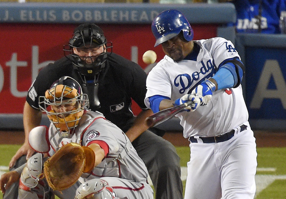 Photo - Los Angeles Dodgers' Juan Uribe, right, hits a two-run home run in front of Washington Nationals catcher Wilson Ramos and home plate umpire Ted Barrett during the sixth inning of a baseball game, Tuesday, Sept. 2, 2014, in Los Angeles. (AP Photo/Mark J. Terrill)