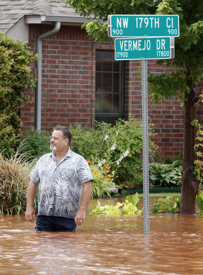 Photo - Frank Kuczinski stands in water outside his house in the Palo Verde Addition in Edmond, OK, after flood waters inundated a number of homes in the area, Monday, June 14, 2010. By Paul Hellstern, The Oklahoman