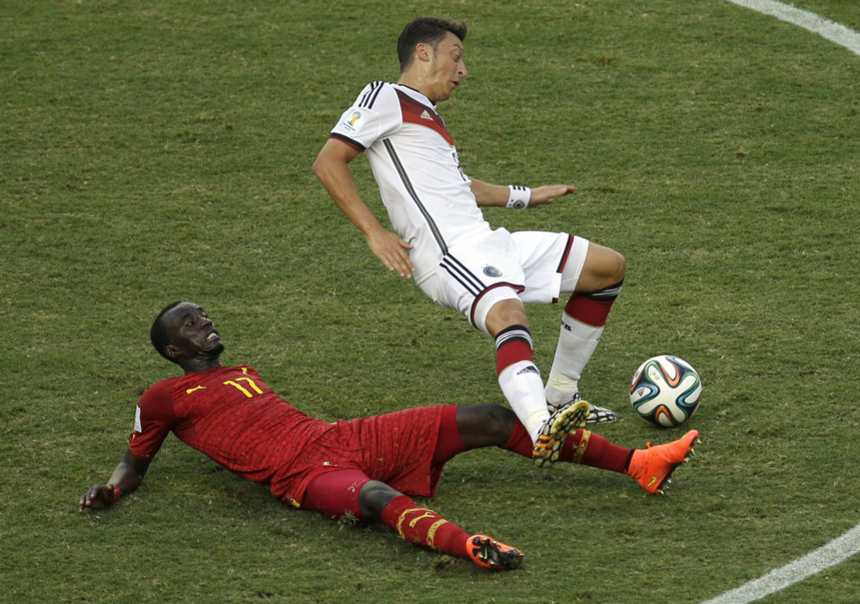 Photo - Germany's Mesut Ozil falls over Ghana's Mohammed Rabiu, bottom, following a tackle during the group G World Cup soccer match between Germany and Ghana at the Arena Castelao in Fortaleza, Brazil, Saturday, June 21, 2014. (AP Photo/Themba Hadebe)