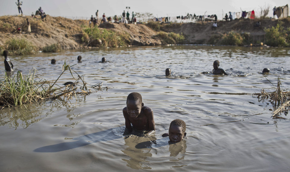Photo - Young displaced boys bathe in a reservoir inside one of the camps for people who have fled the recent violence, in the capital Juba, South Sudan Saturday, Jan. 11, 2014. South Sudanese government troops on Friday retook Bentiu, the capital of oil-producing Unity state, from rebels loyal to the country's former vice president, a military spokesman said, while hundreds of thousands remain displaced in the nearly monthlong conflict. (AP Photo/Mackenzie Knowles-Coursin)