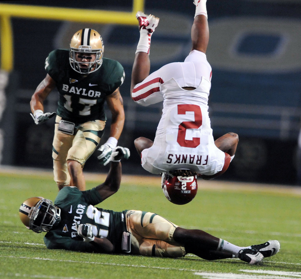 Photo - Oklahoma wide receiver Trey Franks (2) flips over after getting hit by Baylor cornerback Joe Williams (22) in the first half of an NCAA college football game, Saturday, Nov. 19, 2011, in Waco, Texas. (AP Photo/Waco Tribune Herald, Rod Aydelotte)