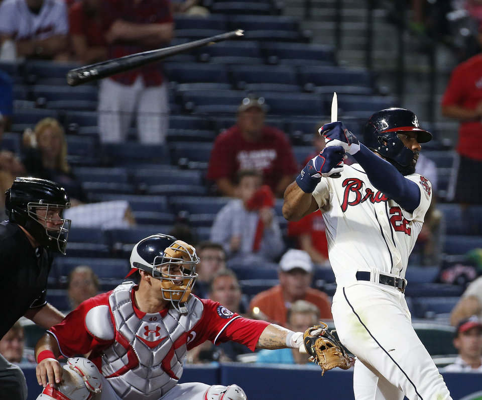 Photo - Atlanta Braves' Jason Heyward breaks his bat as he drives in a run with a sacrifice fly in the sixth inning of a baseball game, in front of Washington Nationals catcher Wilson Ramos early Sunday, Aug. 10, 2014, in Atlanta. (AP Photo/John Bazemore)