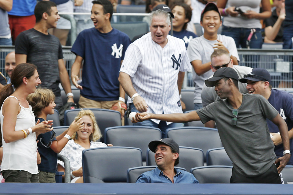 Photo - CORRECTS ASTROS BATTER TO JON SINGLETON, NOT MARWIN GONZALEZ - Comedian Chris Rock, far right, offers a foul ball he caught off  Houston Astros' Jon Singleton to a youngster after catching it in the seventh inning of a baseball game against the New York Yankees at Yankee Stadium in New York, Thursday, Aug. 21, 2014.  (AP Photo/Kathy Willens)