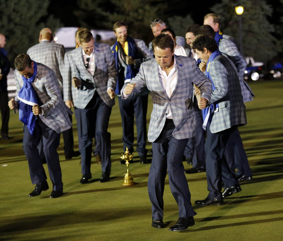 Photo - European players dance around the trophy on the practice green after the Ryder Cup PGA golf tournament Sunday, Sept. 30, 2012, at the Medinah Country Club in Medinah, Ill. (AP Photo/David J. Phillip)  ORG XMIT: PGA255