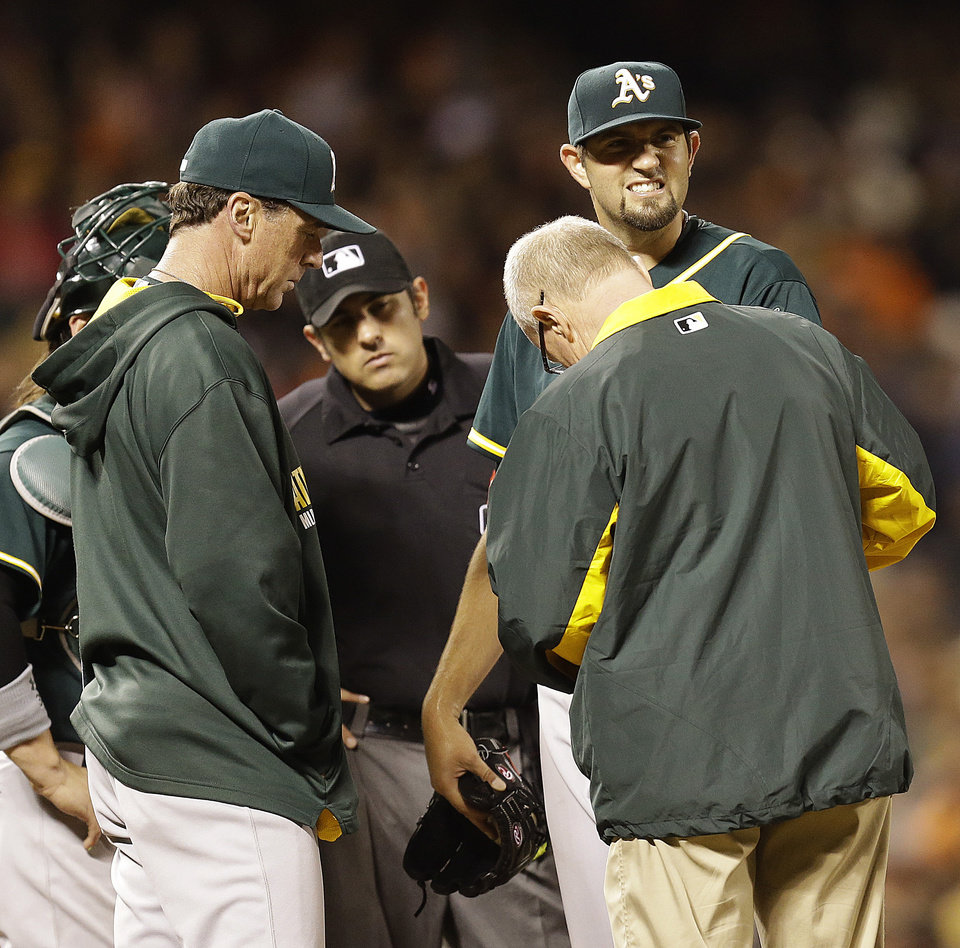 Photo - Oakland Athletics' Jason Hammel, right, is attended to by a trainer after injuring his hand in the fifth inning of a baseball game against the San Francisco Giants, Wednesday, July 9, 2014, in San Francisco. Athletics' manager Bob Melvin, left, looks on. (AP Photo/Ben Margot)