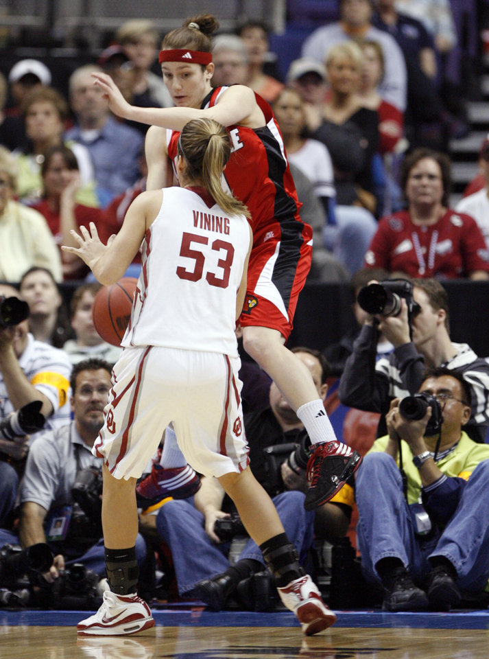 Photo - Becky Burke tries to throw the ball off of Jenny Vining as she steps out of bounds in the first half as the University of Oklahoma plays Louisville at the 2009 NCAA women's basketball tournament Final Four in the Scottrade Center in Saint Louis, Missouri on Sunday, April 5, 2009. 