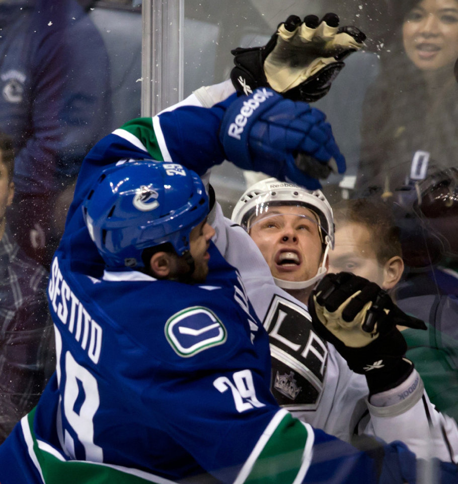 Vancouver Canucks' Tom Sestito, left, and Los Angeles Kings' Jake Muzzin collide during the second period of an NHL hockey game in Vancouver, British Columbia on Saturday, March 2, 2013. (AP Photo/The Canadian Press, Darryl Dyck)