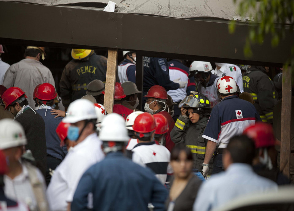 Photo - Rescue workers and firefighters gather at the site of an explosion at an adjacent building to the executive tower of Mexico's state-owned oil company PEMEX, in Mexico City, Thursday Jan. 31, 2013. An explosion at the main headquarters of Mexico's state-owned oil company in the capital killed more than 10 people and injured some 80 as it heavily damaged three floors of the building, sending hundreds into the streets and a large plume of smoke over the skyline. (AP Photo/Eduardo Verdugo)